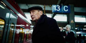 Ein älterer Mann steht an einem Bahnsteig