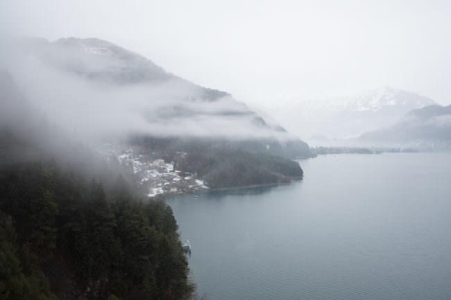 Eine kleine Stadt an einem See im Nebel