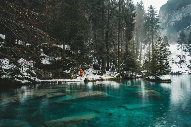 Eine person in roter Jacke steht an einem gefrorenen See