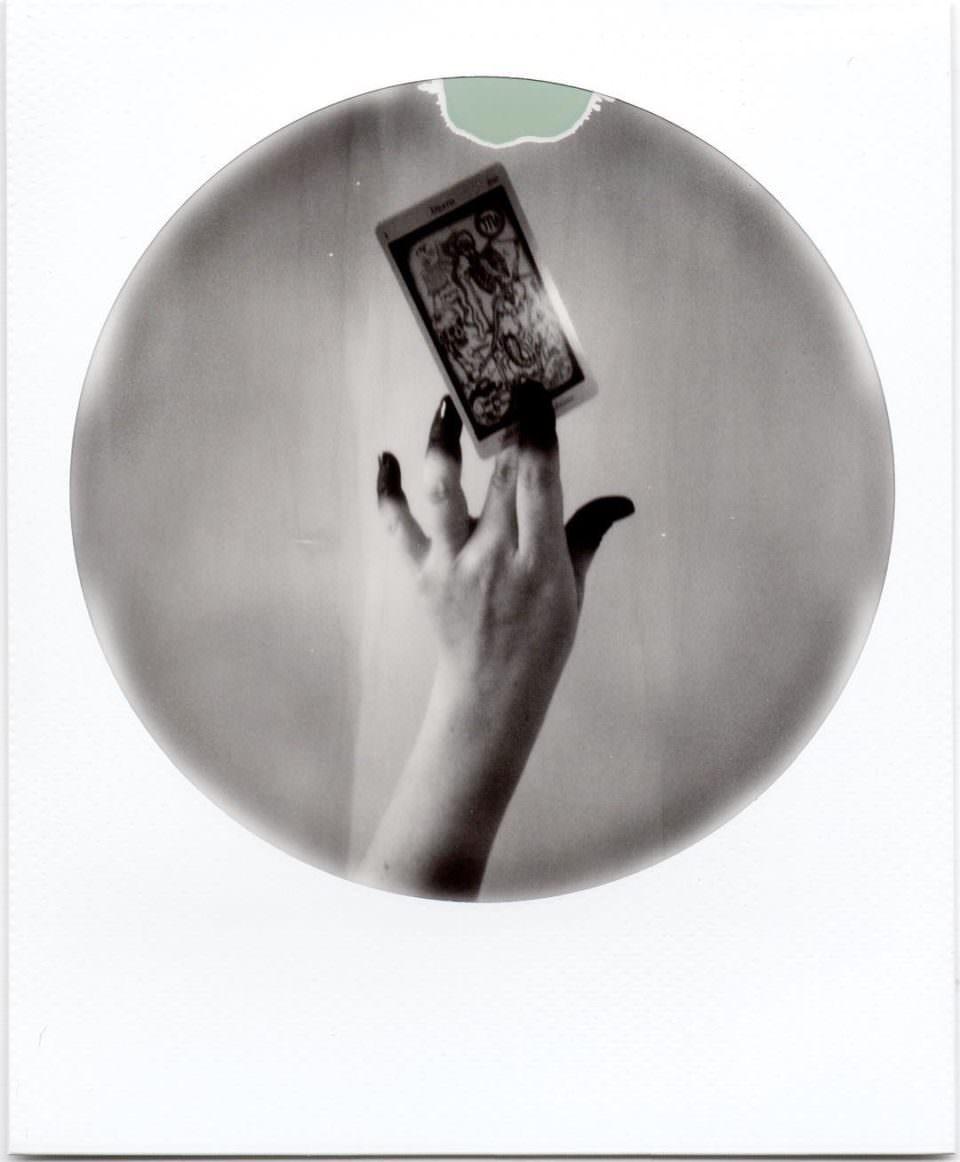 Eine Hand hält eine Spielkarte elegant in die Luft.