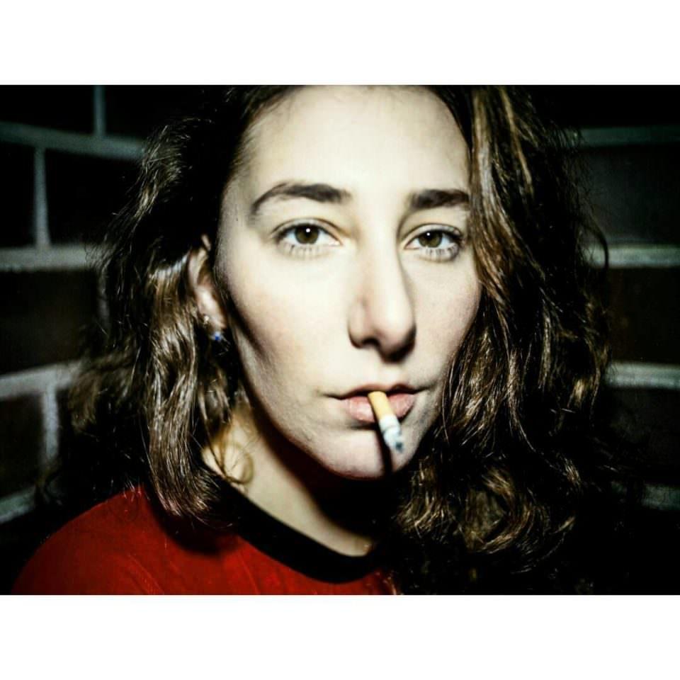 Nahaufnahme des Gesichtes einer jungen, dunkelhaarigen Frau die eine Zigarette im Mund hat.