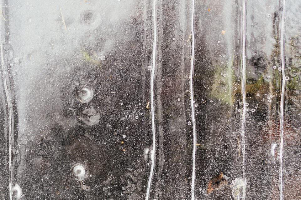 Aufsicht auf eine gefrorene Fläche mit Lufteinschlüssen.