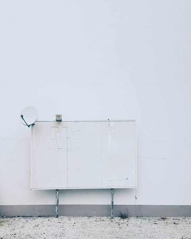 Blick auf eine weiße Wand vor der ein Stromkasten in weiß ist an dem eine Satelitenschüssel befestigt ist.