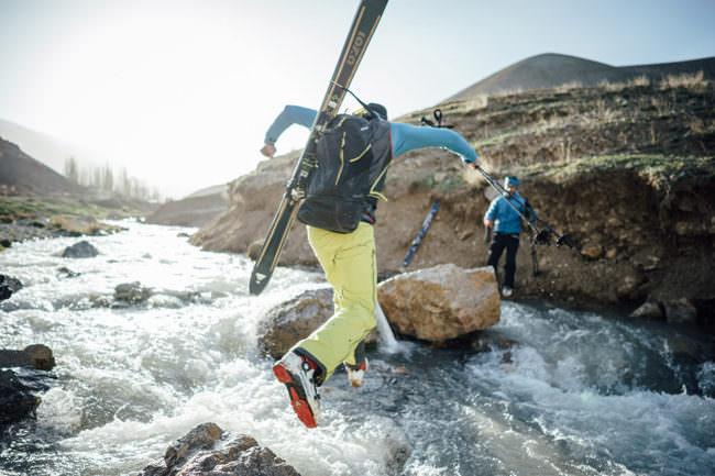 Ein Mann springt über einen Fluss