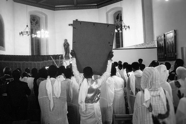 Ein Mann hält ein Schild in einer Kirche nach oben