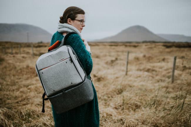 Eine Frau, die einen grauen Rucksack auf einer Schulter trägt und vor einer Landschaft mit Bergen steht.