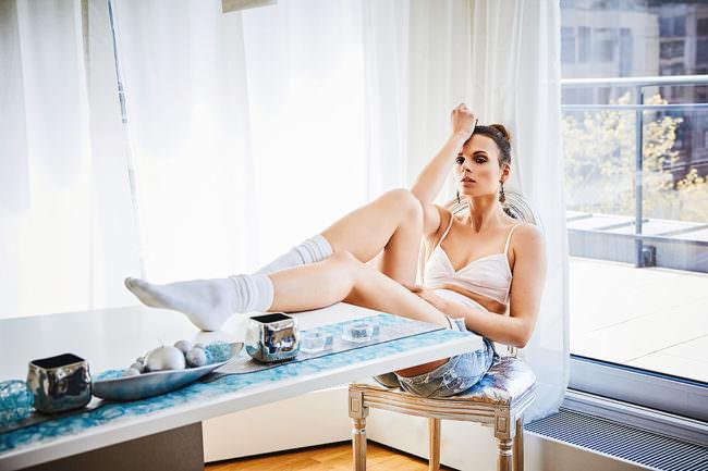 Eine Frau in Unterwäsche und Socken am Tisch