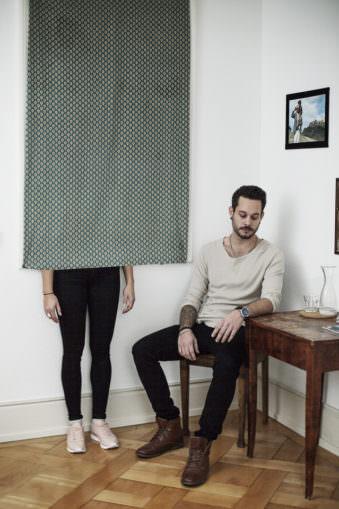 Ein Mann am Tisch und eine Frau hinter einem Vorhang