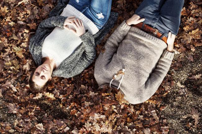 Ein Mann und eine Frau liegen im Laub