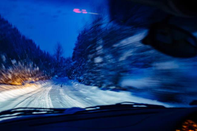Eine verschneite Straße aus dem Auto heraus aufgenommen
