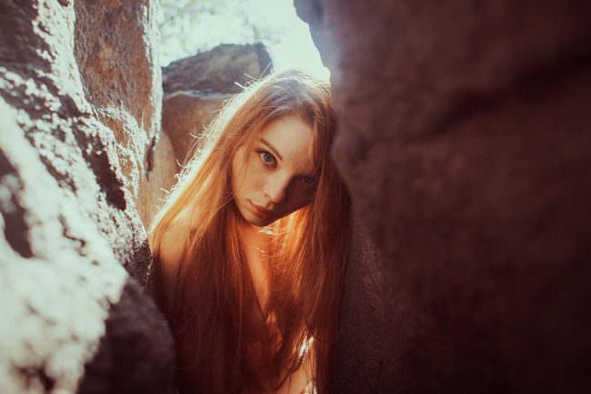 Eine Frau lehnt an Felsen