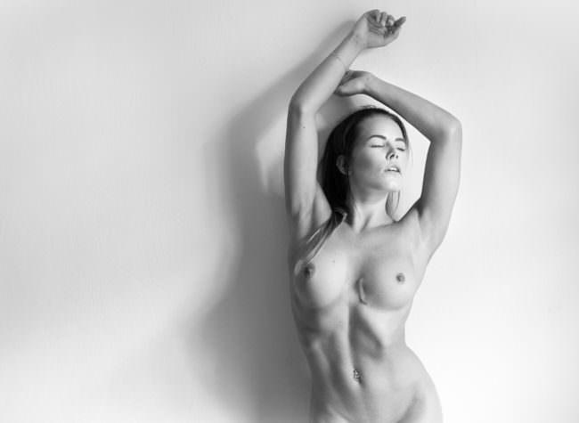 Eine nackte Frau lehnt an einer Wand