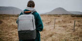Eine Frau mit einem grauen Rucksack steht vor einer Landschaft mit Bergen.