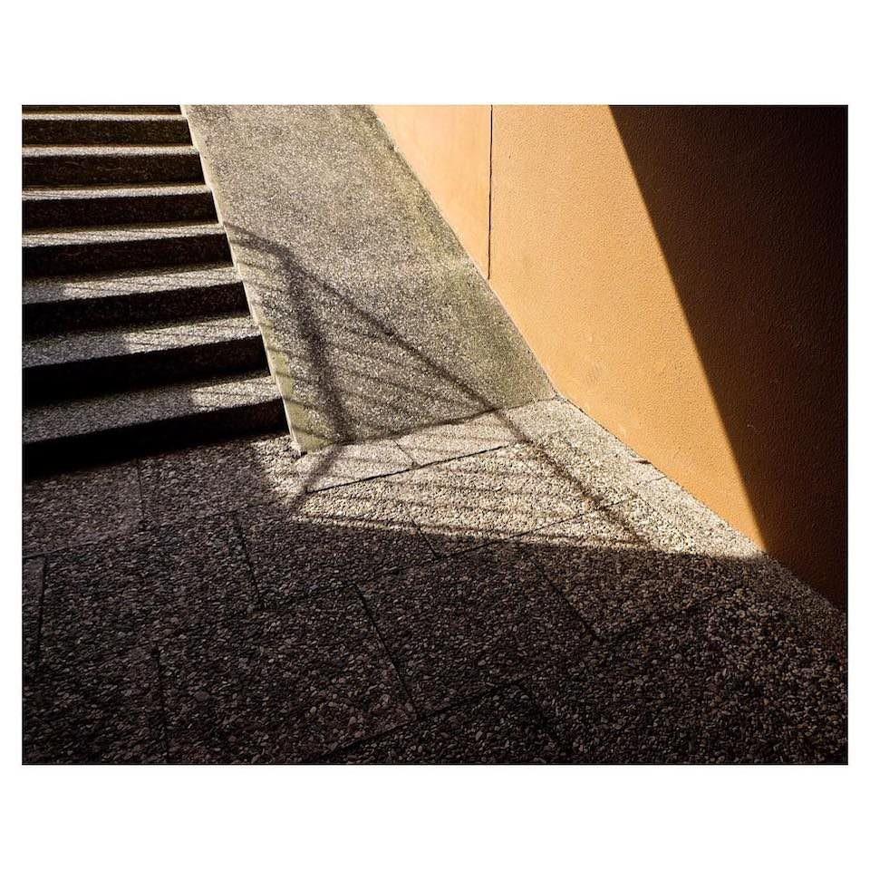 Schatten, der auf den Fuss einer Treppe trifft.