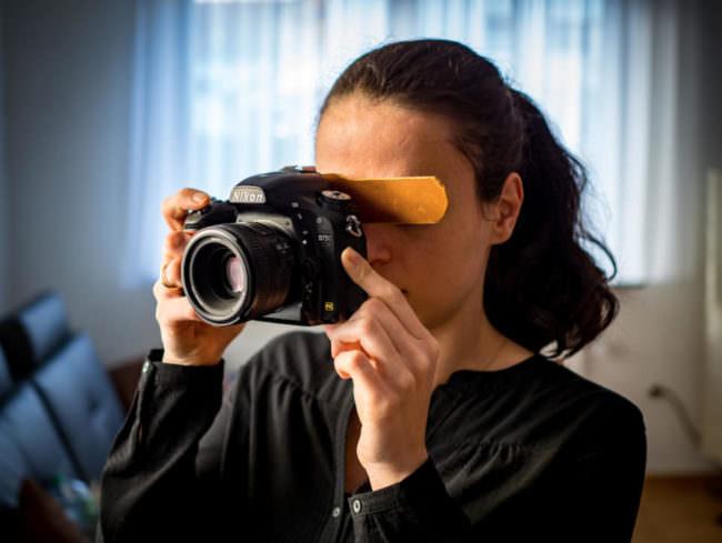 Eine Frau die durch eine Kamera sieht an der ein Eyecatchr angebracht ist.