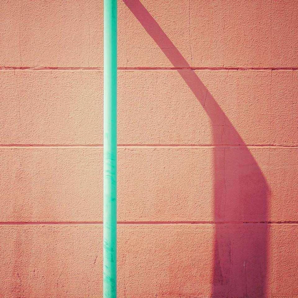 Eine grüne Stange vor einer orangen Wand.