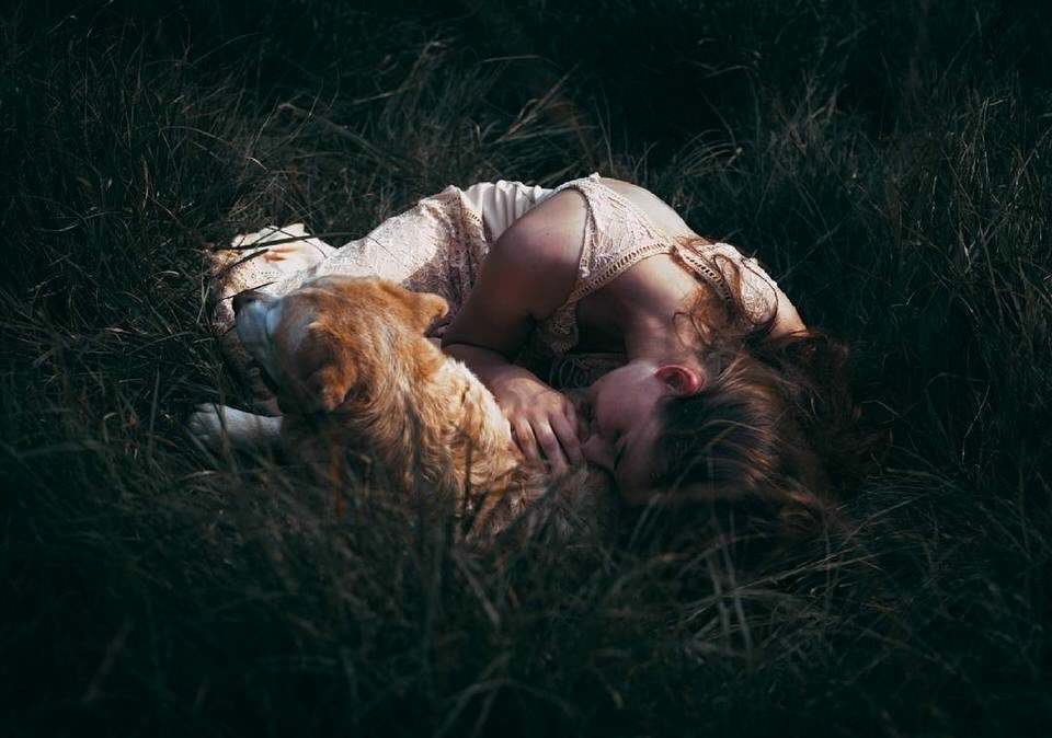 Eine Frau mit Hund liegt im Gras