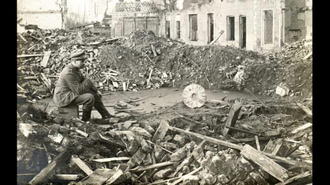 Historisches Bild aus dem Ersten Weltkrieg mit einem Mann, der auf einem Trümmerhaufen sitzt.