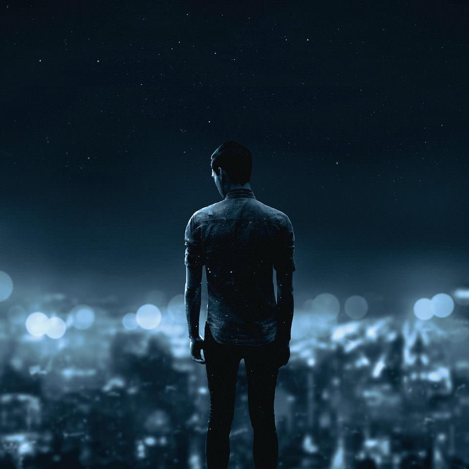 Ein Mann steht vor einer Stadt im Bokeh unter einem Sternenhimmel