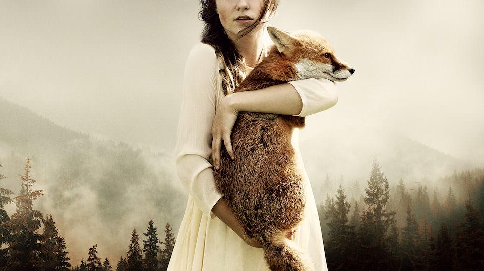 Eine Frau die vor einem Wald steht und einen Fuchs hochhält.