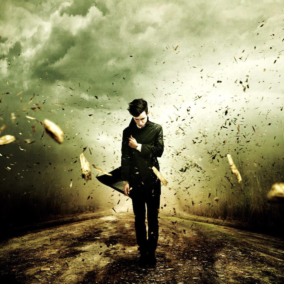 Ein Mann in einem schwarzen Mantel läuft durch fliegende Holzsplitter.