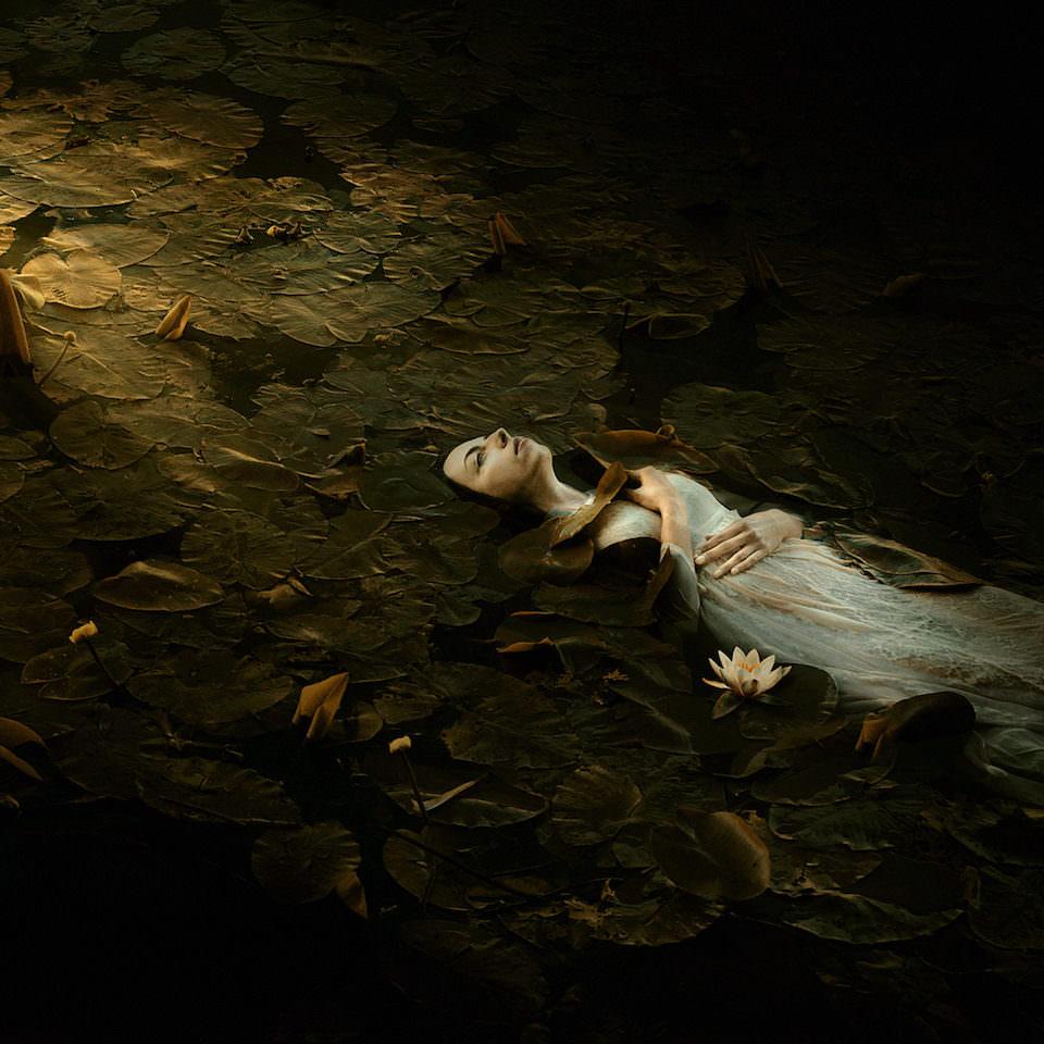 Eine Frau die in einem See zwischen Seerosen liegt.