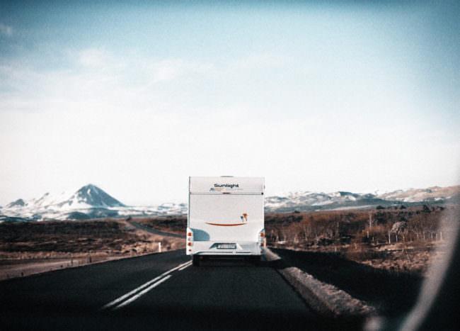 Ein Wohnwagen fährt auf einer Straße vor einem Bergpanorama.
