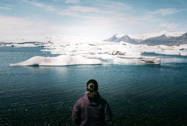 Ein Mensch steht vor einer Eislandschaft und blickt darauf.