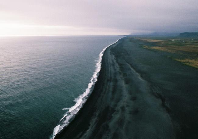 Ein Strand mit schwarzem Sand von oben.