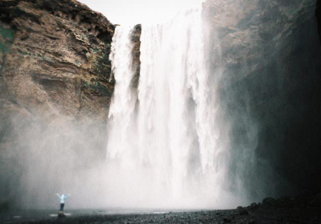 Ein Mensch steht vor einem Wasserfall.