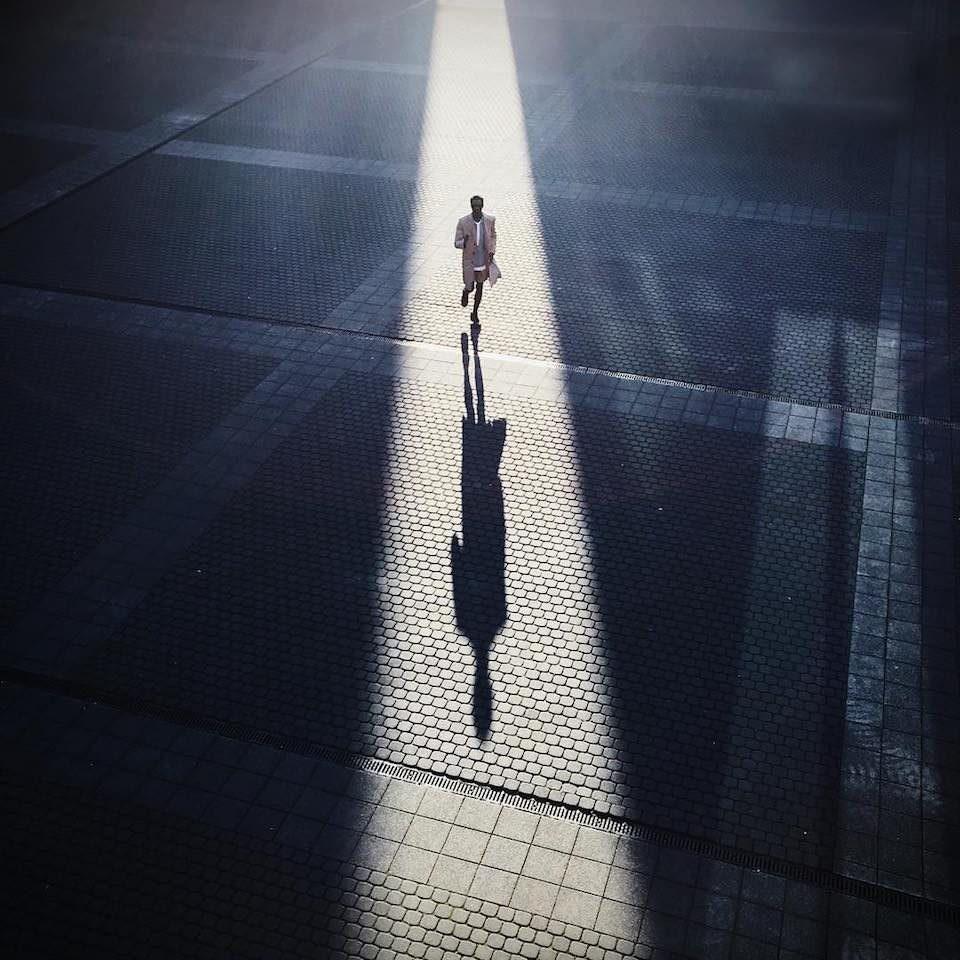 Mann läuft zwischen zwei Schatten entlang.