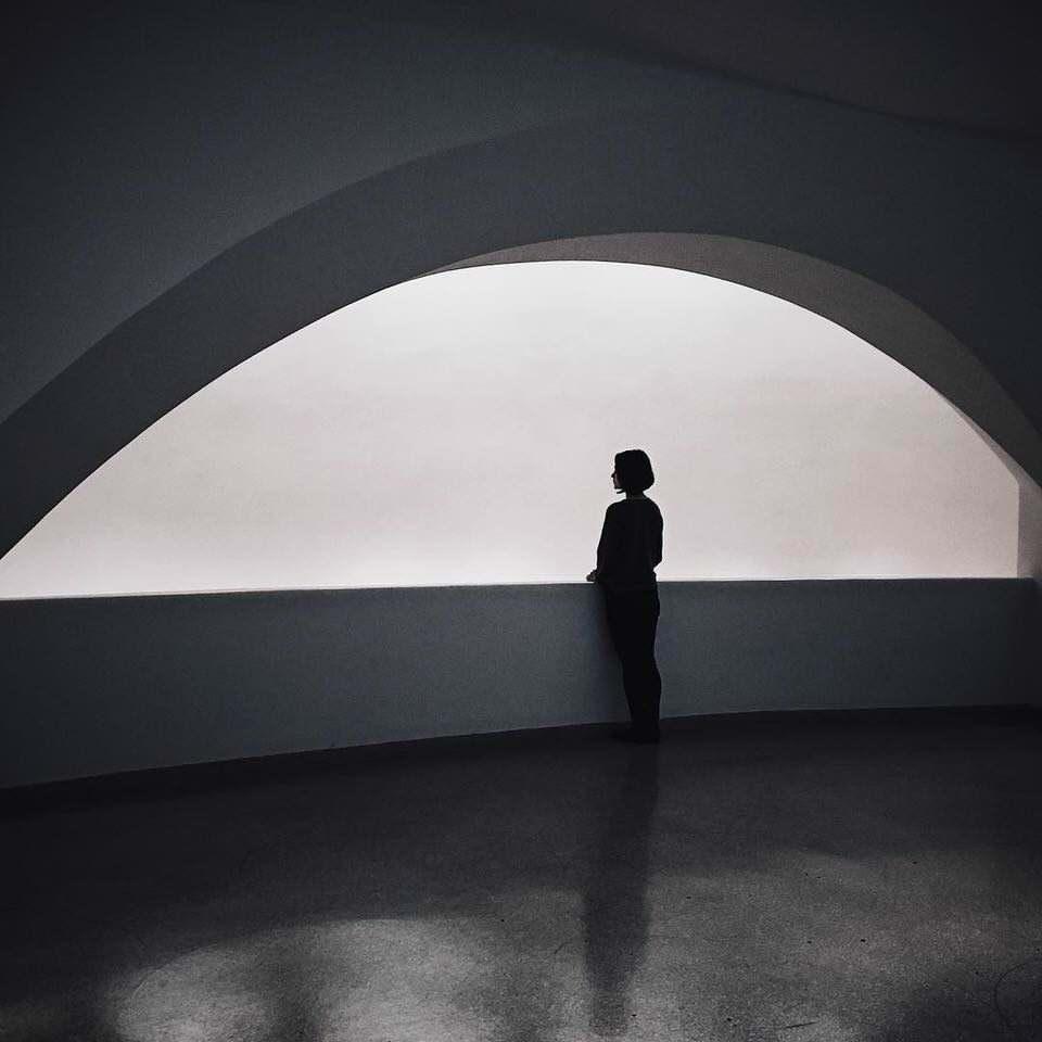 Eine Frau vor einer halbrunden Wand