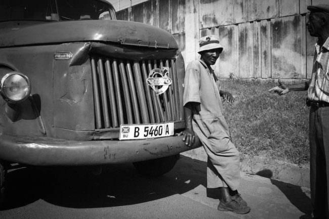 Straßenszene mit einem Mann, der an der Motorhaube eines alten Lastwagens lehnt.