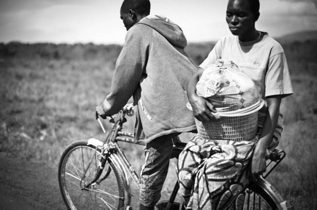 Zwei Jungen fahren auf einem Fahrrad.