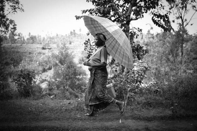 Eine Frau die sich mit einem großen Schirm vor der Sonne schützt geht einen Weg entlang.