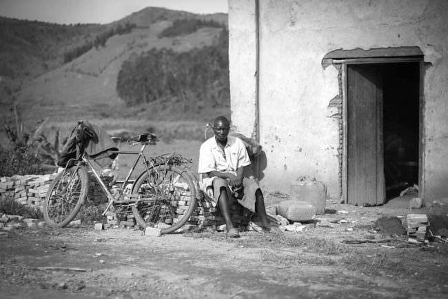 Ein Mann sitzt vor einem heruntergekommenen Haus, neben Ihm steht ein Fahrrad.