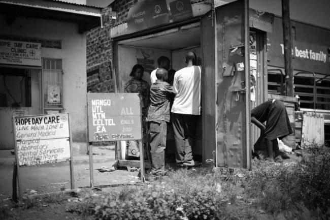 Mehrere Menschen drängen sich in den Eingang einer Kindertagesbetreuung.