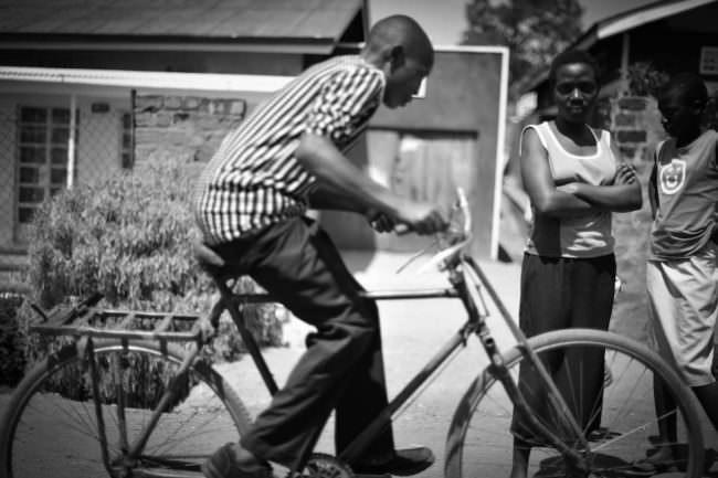 Ein Mann fährt auf einem Fahrrad während eine Frau daneben steht und in die Kamera blickt.
