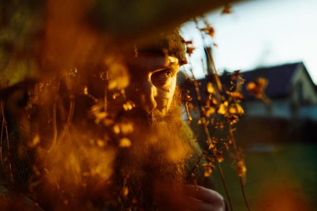 Eine Person hinter Blättern in der Abendsonne