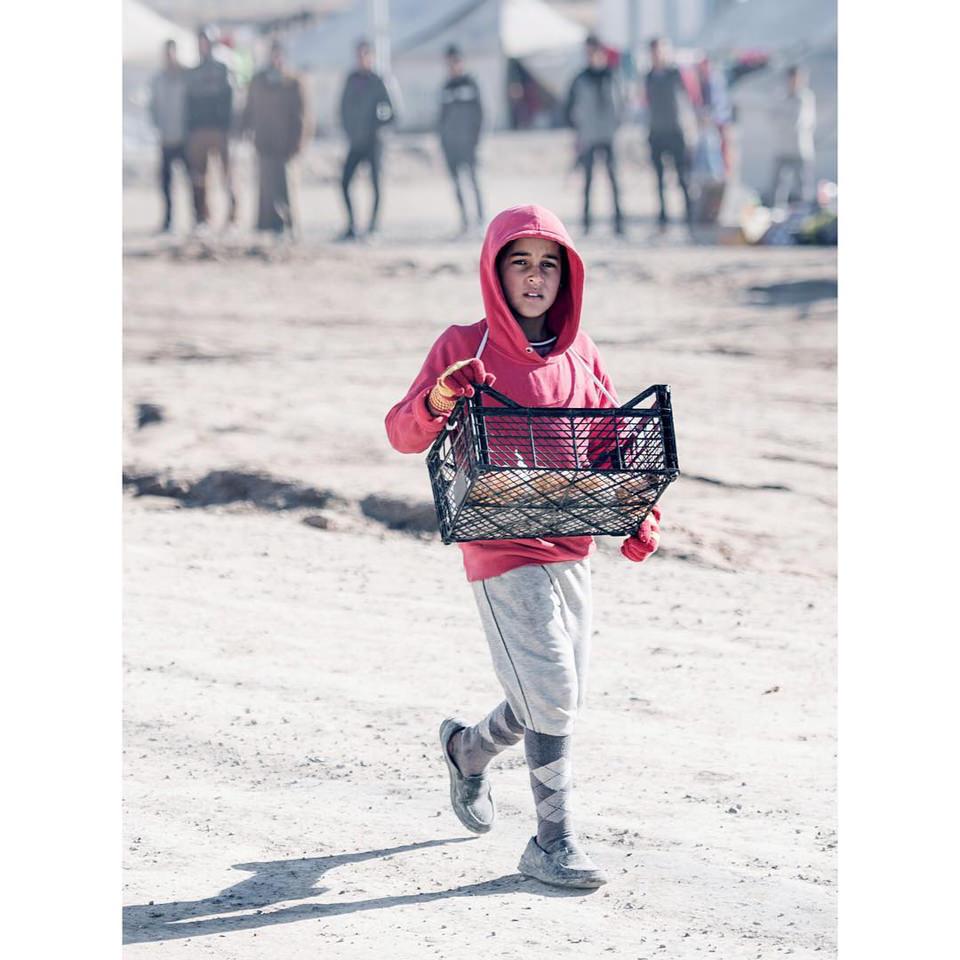 Ein Junge trägt eine Kiste