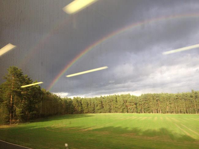 Aufnahme eines Regenbogens in der Landschaft mit Lichtreflexionen auf einer Scheibe.
