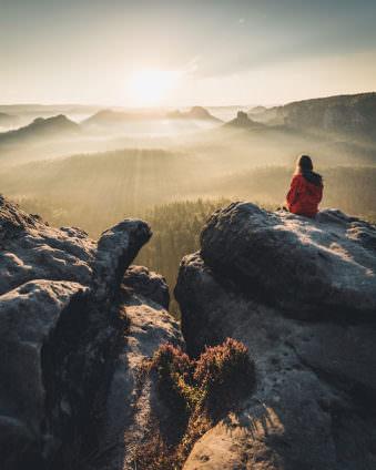 Berglandschaft im Sonnenlicht mit einer Person die auf einem Felsen sitzt.