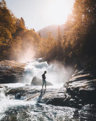 Lichtdurchflutete Berglandschaft mit Fluss in der Mitte, in dem eine Person steht.