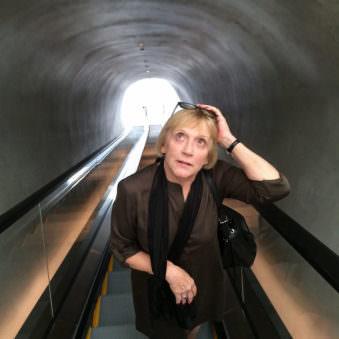 Frau auf einer Rolltreppe in einem Tunnel von vorn fotografiert.