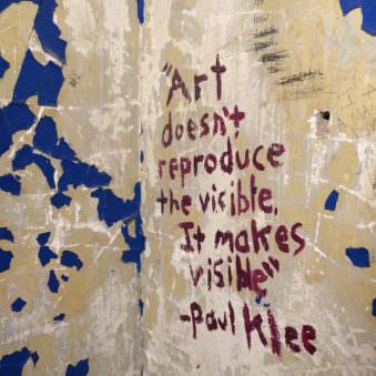 Hausecke mit abgeblätterter Farbe und einem hufgepinselten Zitat von Paul Klee.