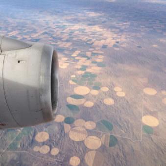 Sicht auf einem Flugzeug mit angeschnittener Turbine und runden Feldern am Boden.