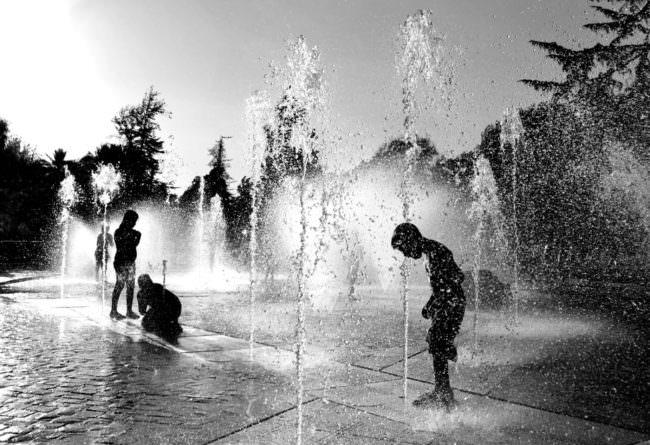 Kinder spielen in Springbrunnen