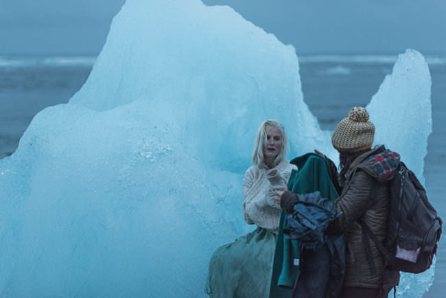 Eine Frau an einem Eisberg zieht ihre Jacke aus