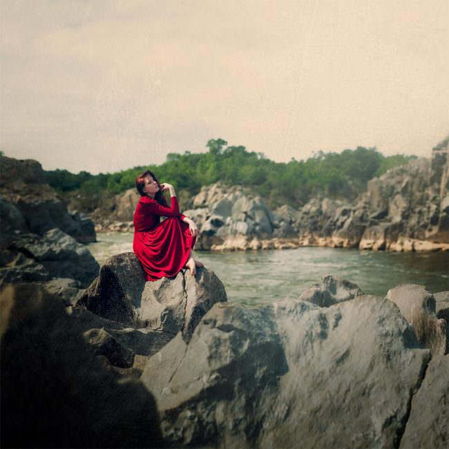 Eine Frau im roten Kleid auf Felsen am Fluss