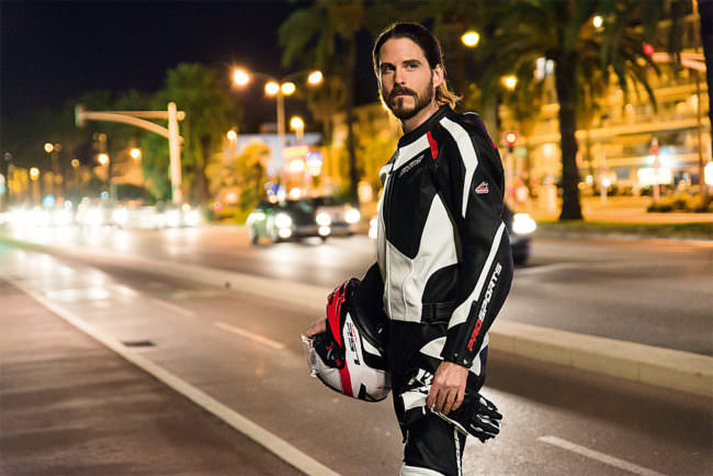Mann in Motorradkluft am Straßenrand